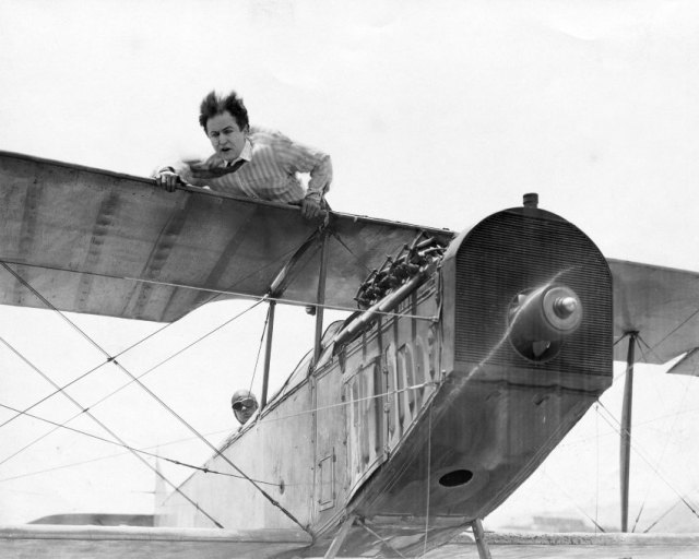ca. 1919 --- Harvey Hanford (Harry Houdini) lays atop a plane's wings. --- Image by © John Springer Collection/CORBIS