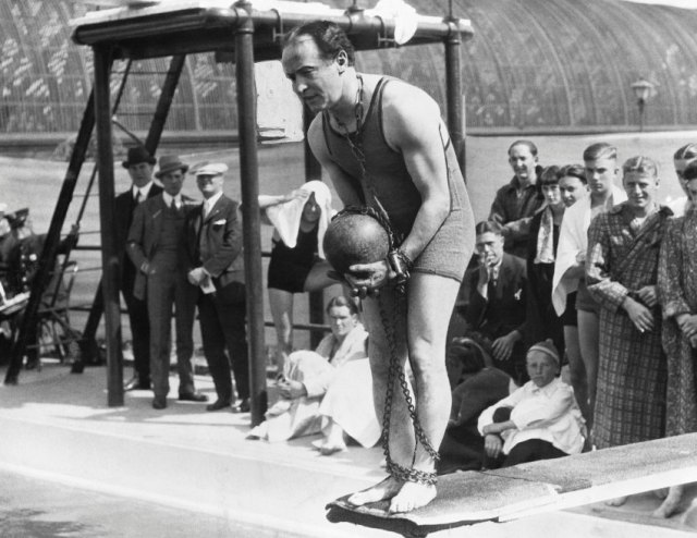ca. 1920s --- Original caption: Portrait of famous escape artist Harry Houdini on diving board with ball and chain. --- Image by © Bettmann/CORBIS